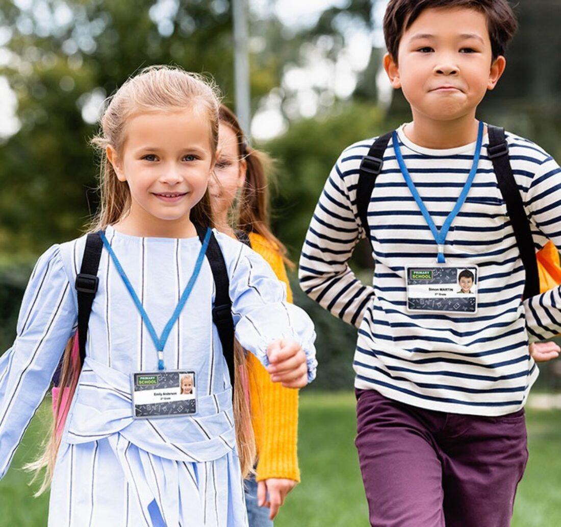 two children walking to their school wearing their school badge